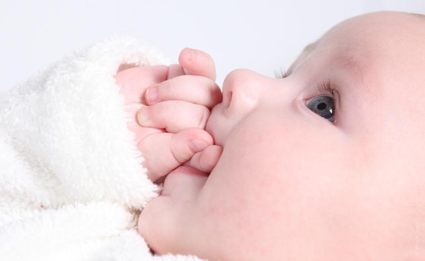 Новорожденный с ручкой во рту